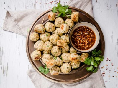 Asian Chicken Meatballs piled on a plate with dipping sauce