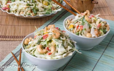Two small white bowls of salad garnished with cashews