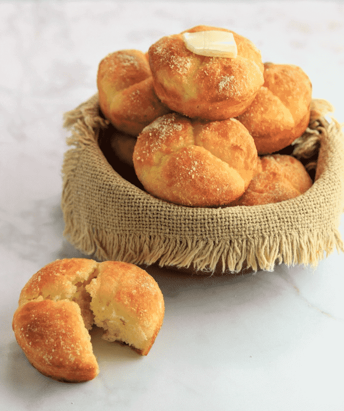 Pull-apart clover rolls inside of a basket with butter on top