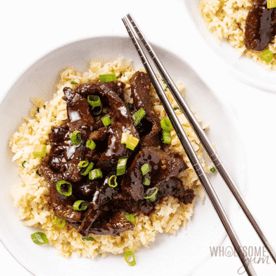 Keto Slow Cooker Mongolian Beef in a white bowl with metallic chopsticks.