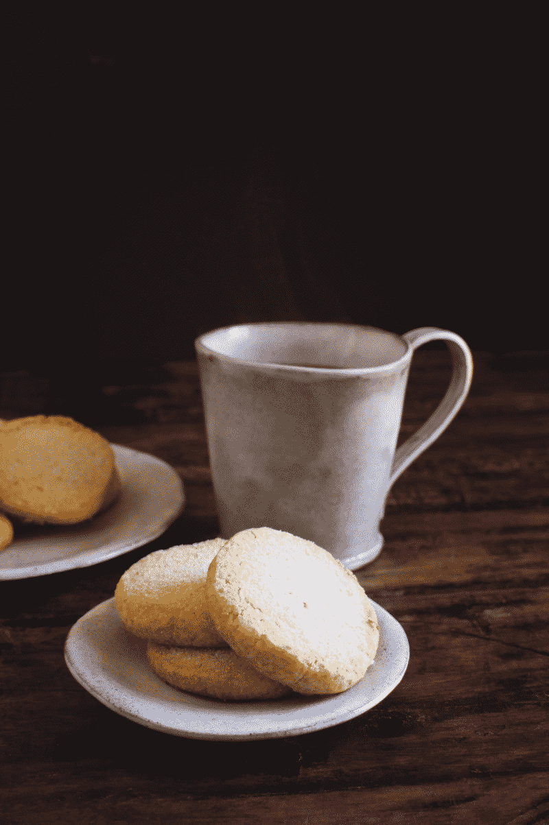 Low-carb sugar cookies on small plates next to a teacup
