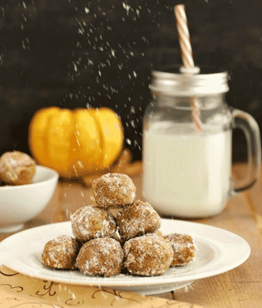 Pumpkin pie snowball cookies on a white plate with a glass of milk