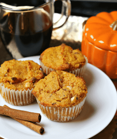 Keto Pumpkin Spice Muffins on a tray with cinnamon sticks and coffee