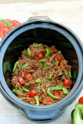 Slow Cooker Harissa Pulled Beef in a blue crockpot, garnished with tomatoes and bell pepper.