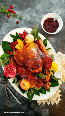THE BEST BRINED WHOLE TURKEY on a white plate, on top of a bed of leafy greens