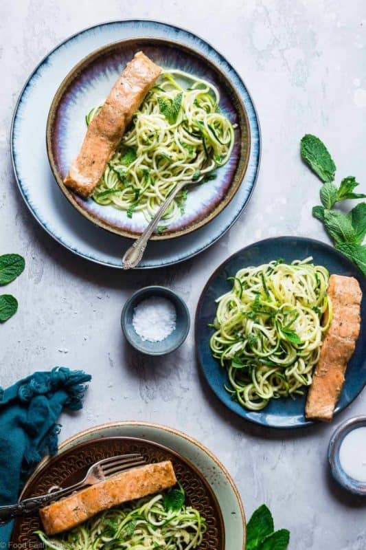 Cooked salmon and zucchini noodles on plates