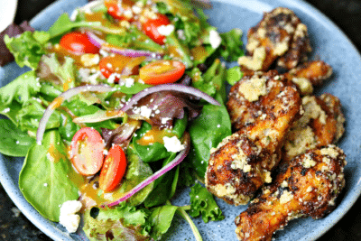Garlic Parmesan Wings on a plate with a salad