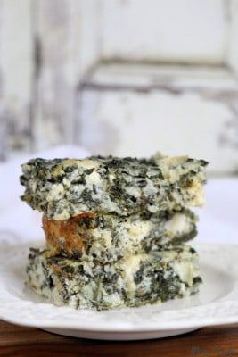 A stack of three Spanakopita Cottage Cheese and Egg Casserole pieces on a white plate