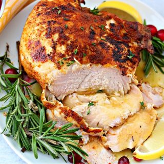 turkey breast on a plate with gravy and cranberry sauce
