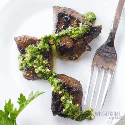 Low Carb STEAK BITES APPETIZER RECIPE WITH CHIMICHURRI DIPPING SAUCE on a white plate with a fork