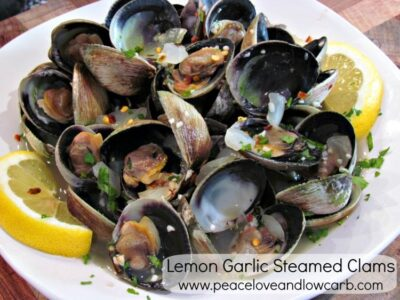 Lemon Garlic steamed clams on a white plate garnished with lemon slices.