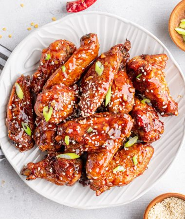 asian sticky wings on a plate with sesame seeds and green onions on the side