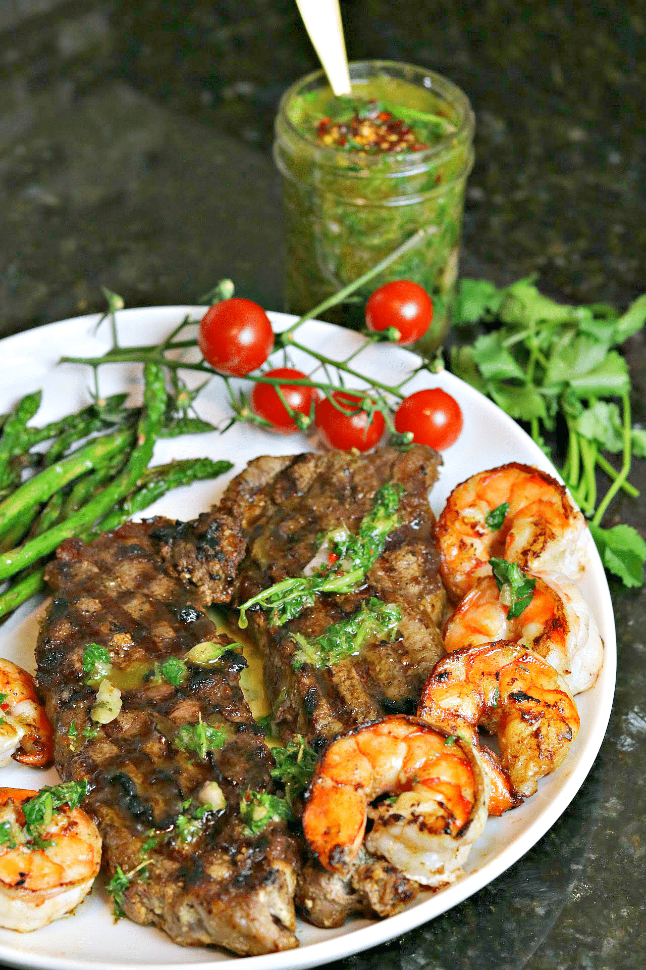 NY Strip Steak on a plate with asparagus, shrimp, and chimichurri