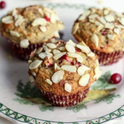 Three delicious looking Cranberry Almond Crumb Muffins on a festive plate, ready to eat.