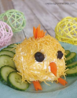 An Easter-themed chick shaped Cheese ball with sliced vegetables.
