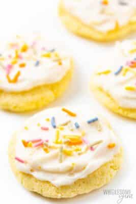 Beautifully decorated iced keto sugar cookies on a plate.