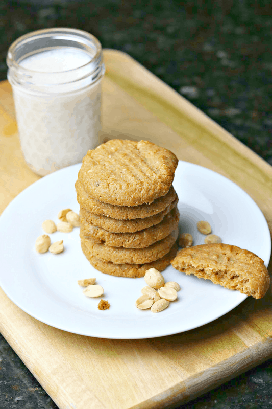 low carb peanut butter cookies stacked on a plate with almond milk