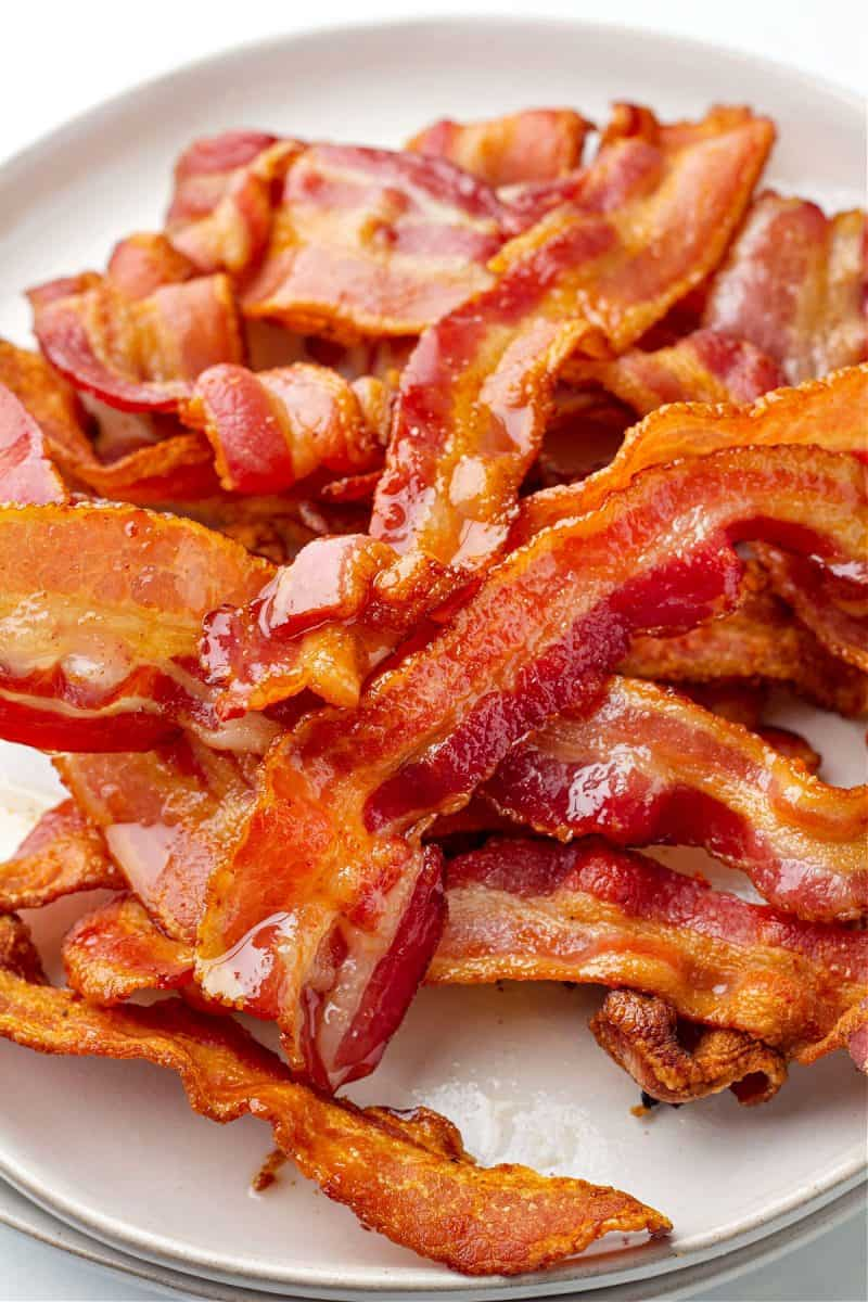 a plate filled with a pile of cooked bacon