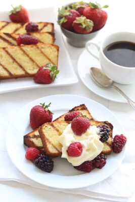 Grilled Pound Cake with Mixed Berries on a white plate and a cup of coffee on the side