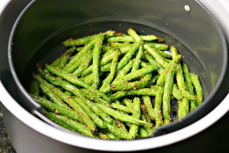 a close-up of crispy green beans in a Ninja Foodi air fryer cooking basket