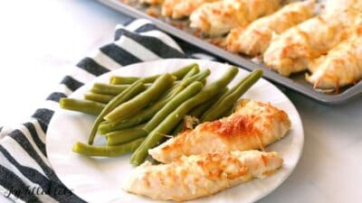Garlic Parmesan Chicken tenders on a plate with green beans