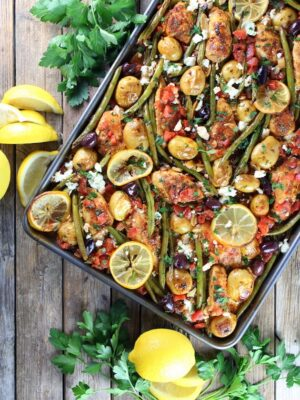 greek chicken on a sheet pan with lemon, herbs and vegetables