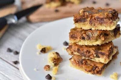 A stack of Keto Chocolate Chip Pumpkin Pecan Bars on a white plate