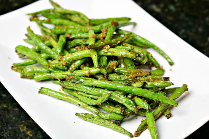 A close up of Green beans made in an air fryer on a white plate