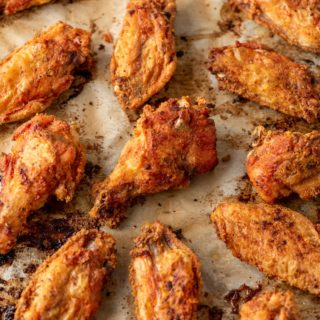 crispy baked chicken wings on a parchment lined baking sheet