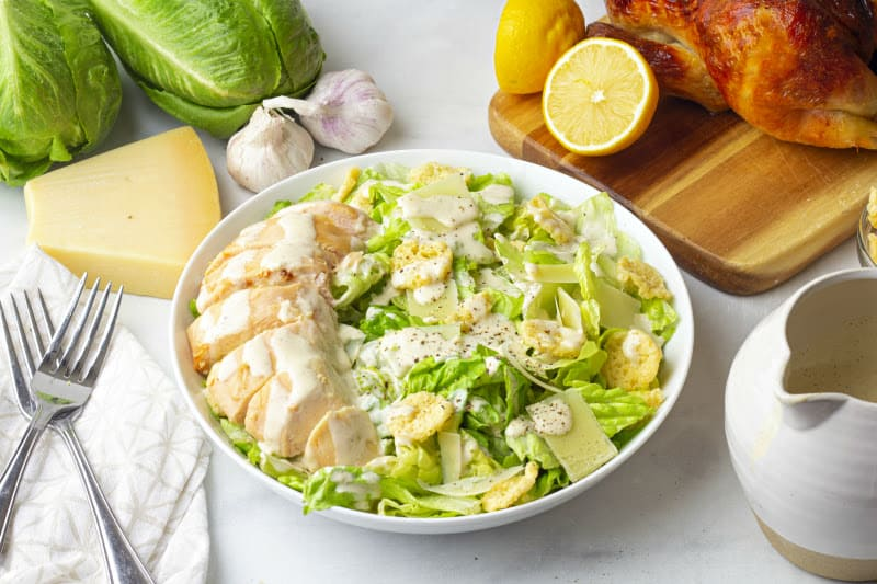 One bowl of Chicken Caesar Salad with lettuce and rotisserie chicken in the background