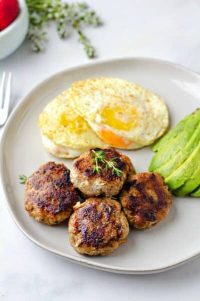 four chicken breakfast sausages on a plate with avocado & eggs
