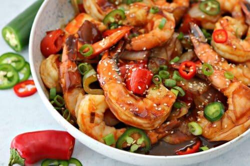 A bowl of food on a plate, with keto sweet and sour shrimp, sliced peppers, and sesame seeds