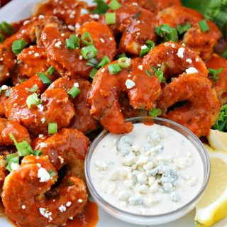 One plate of buffalo shrimp with blue cheese dressing dip and sliced lemons