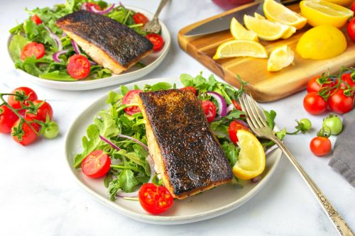Two plates of crispy skin salmon topped in a veggie salad