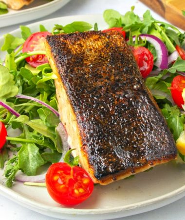 One plate of crispy skin salmon topped in a veggie salad