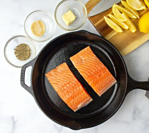 Two Salmon Filets in a pan next to a chopping board with slices of lemon