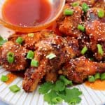 a close-up of honey sriracha chicken wings on a plate topped with green onions and sesame seeds