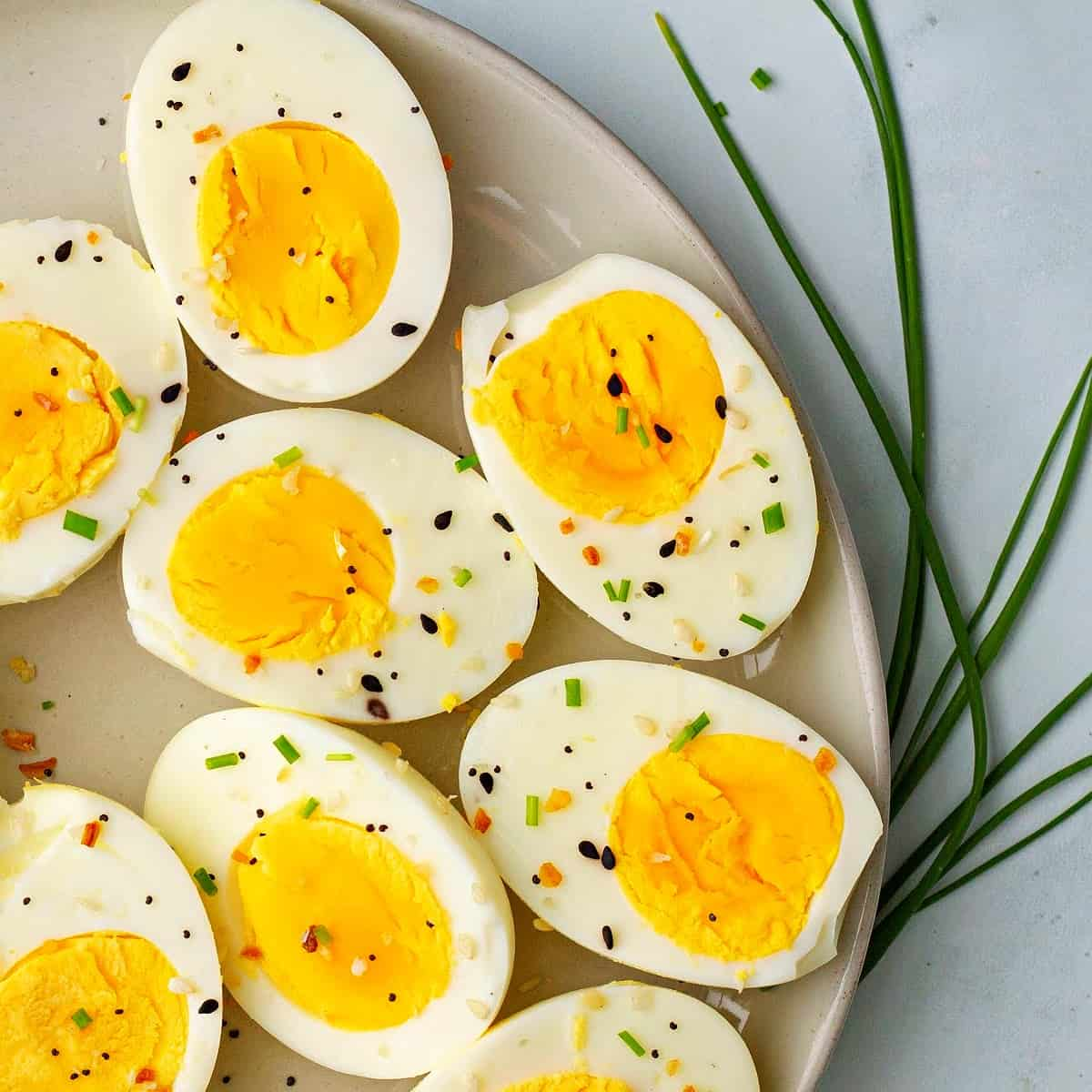 a close-up of hard boiled eggs on a plate topped with chives and everything bagel seasoning