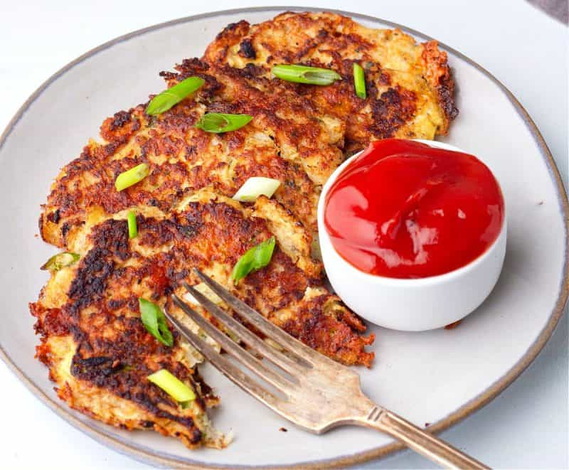 three cauliflower hash browns on a plate with no sugar added ketchup