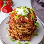 a close up of a stack of cauliflower hash browns on a plate topped with sour cream and green onions