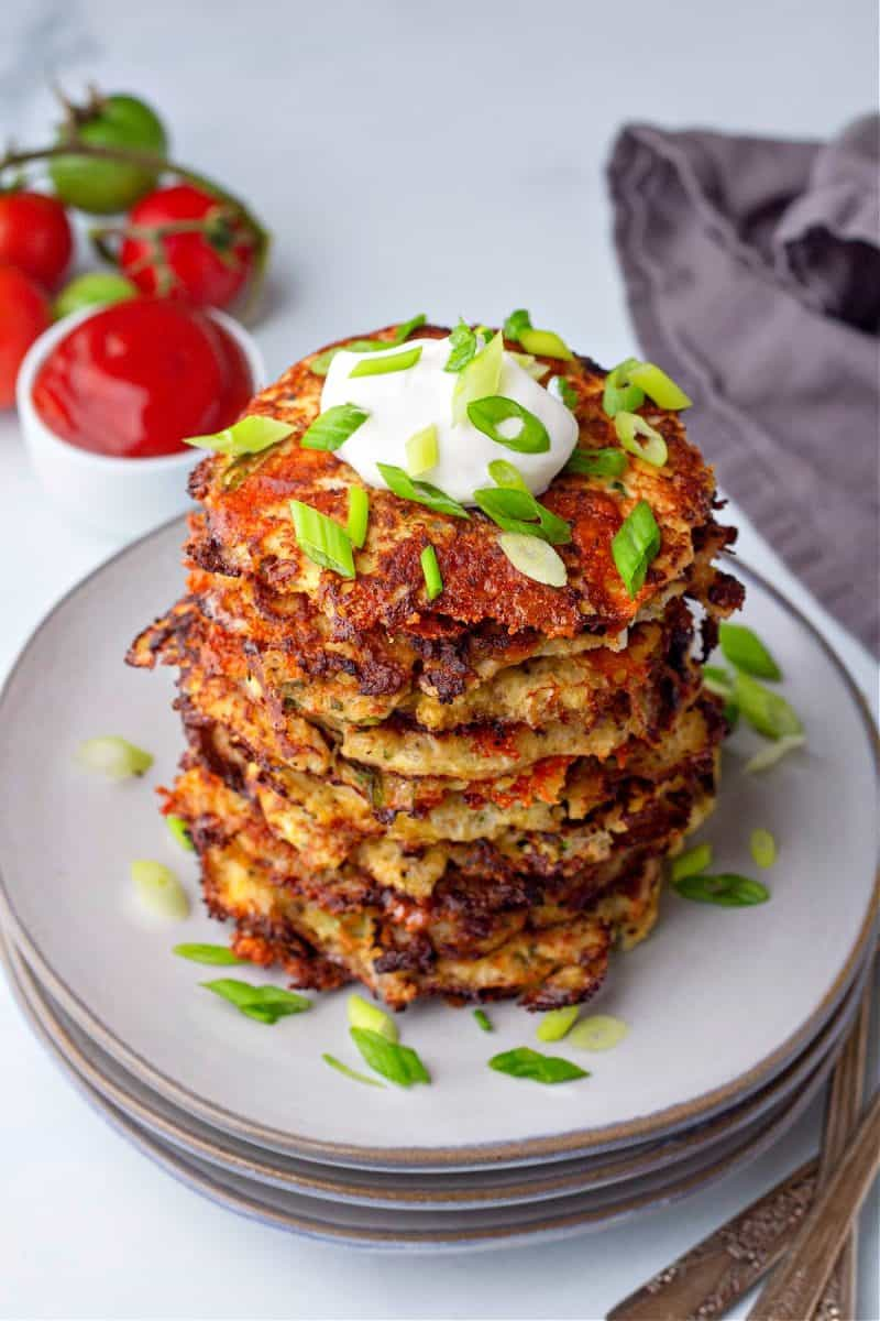 a vertical close up of a stack of cauliflower hash browns on a plate topped with sour cream and green onions
