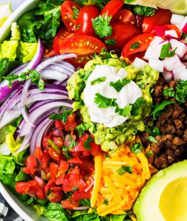 keto taco salad in a bowl with avocado, Pico De Gallo, taco meat, cheddar, lettuce, and red onions