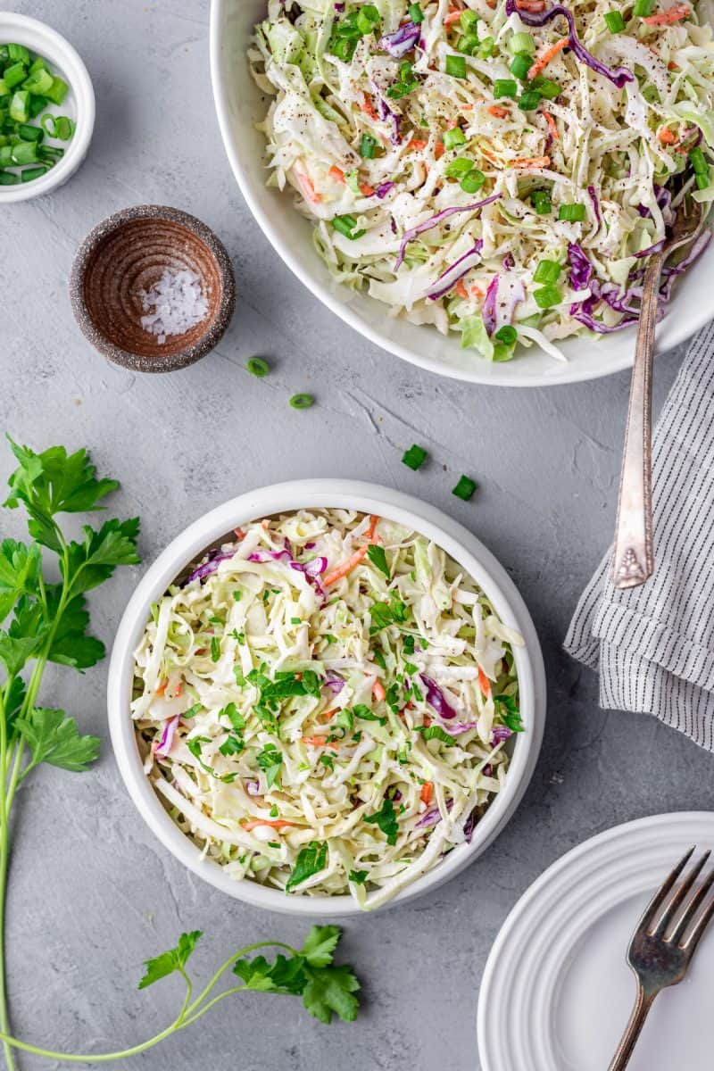 two bowls of keto coleslaw with green onions and salt