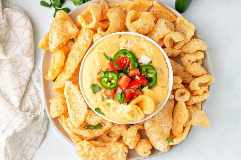 close up of keto queso in a bowl with pork rinds