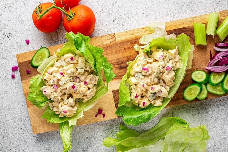 two tuna salad lettuce wraps on a cutting board with tomatoes