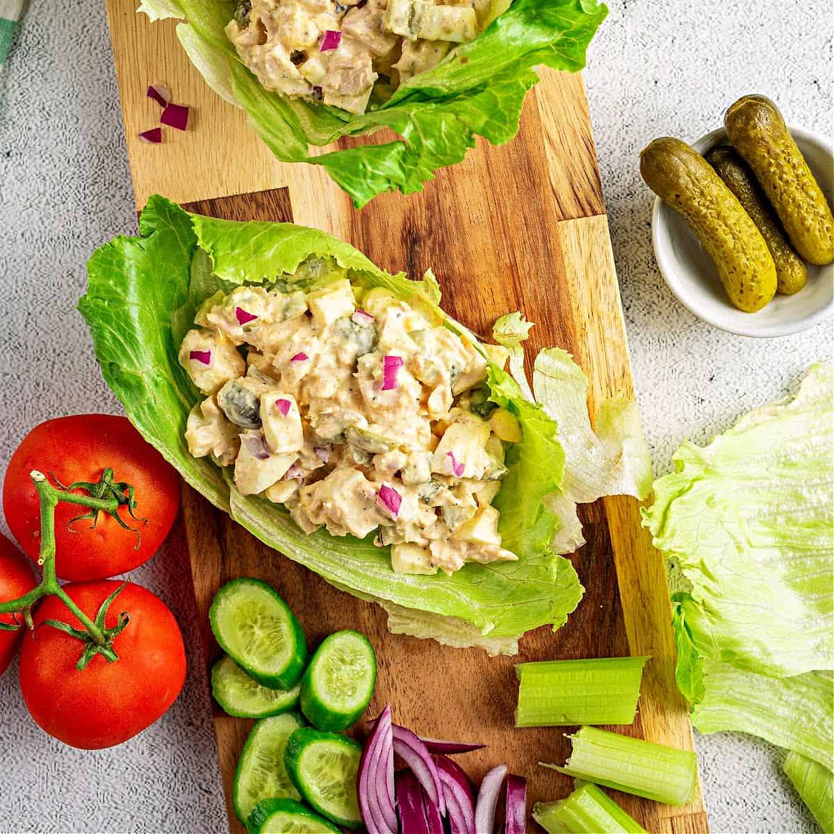 a close up of a tuna salad lettuce wrap on a cutting board with chopped vegetables