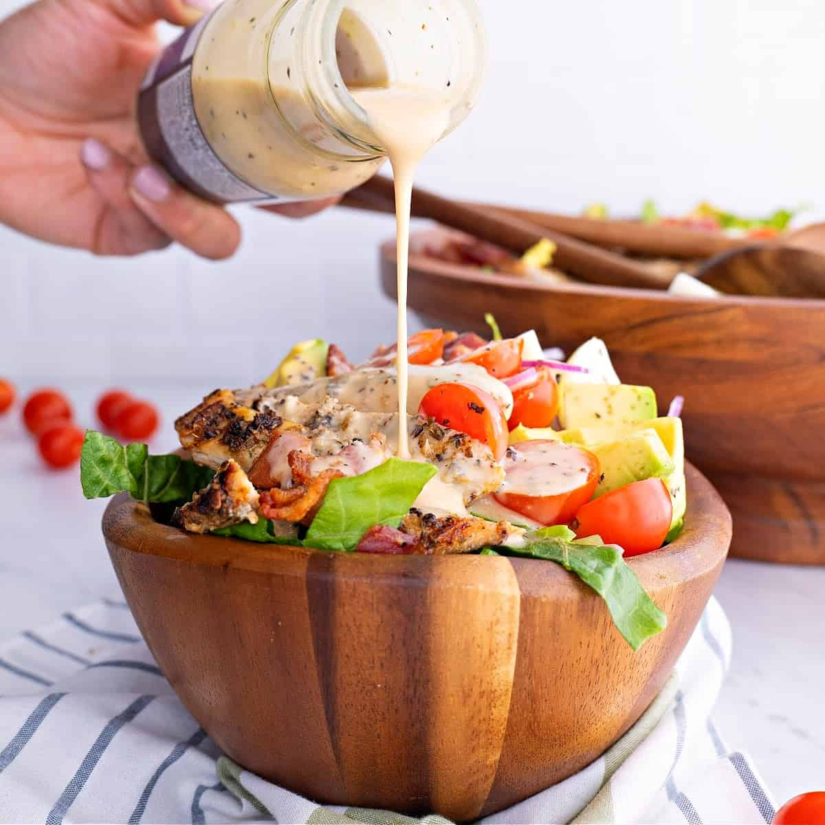 a close-up of Keto Cobb Salad in a brown bowl with dressing being poured on top