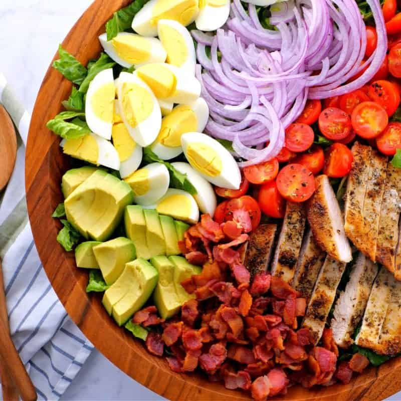 a close-up of a Chicken Cobb Salad with eggs, avocado, bacon, red onions, and cast iron skillet chicken breast in a brown bowl