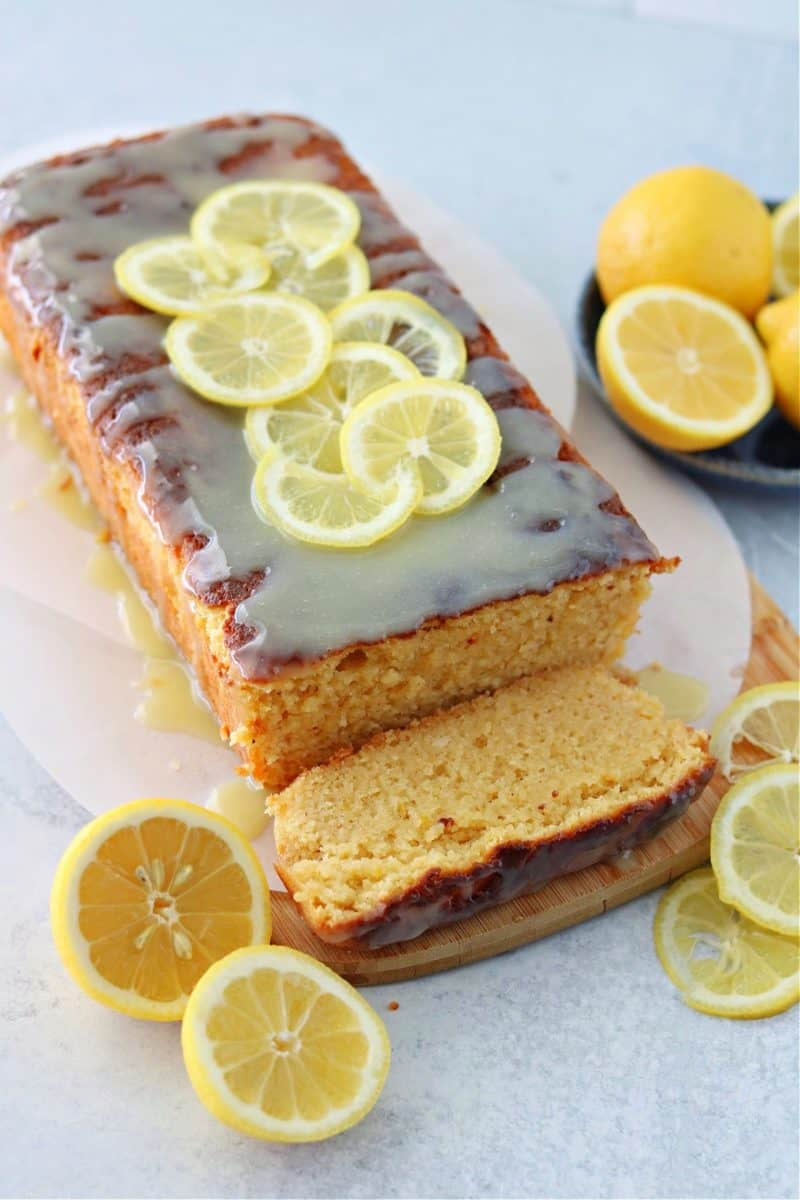 vertical image of keto lemon pound cake on top of a brown cutting board with a keto white chocolate glaze
