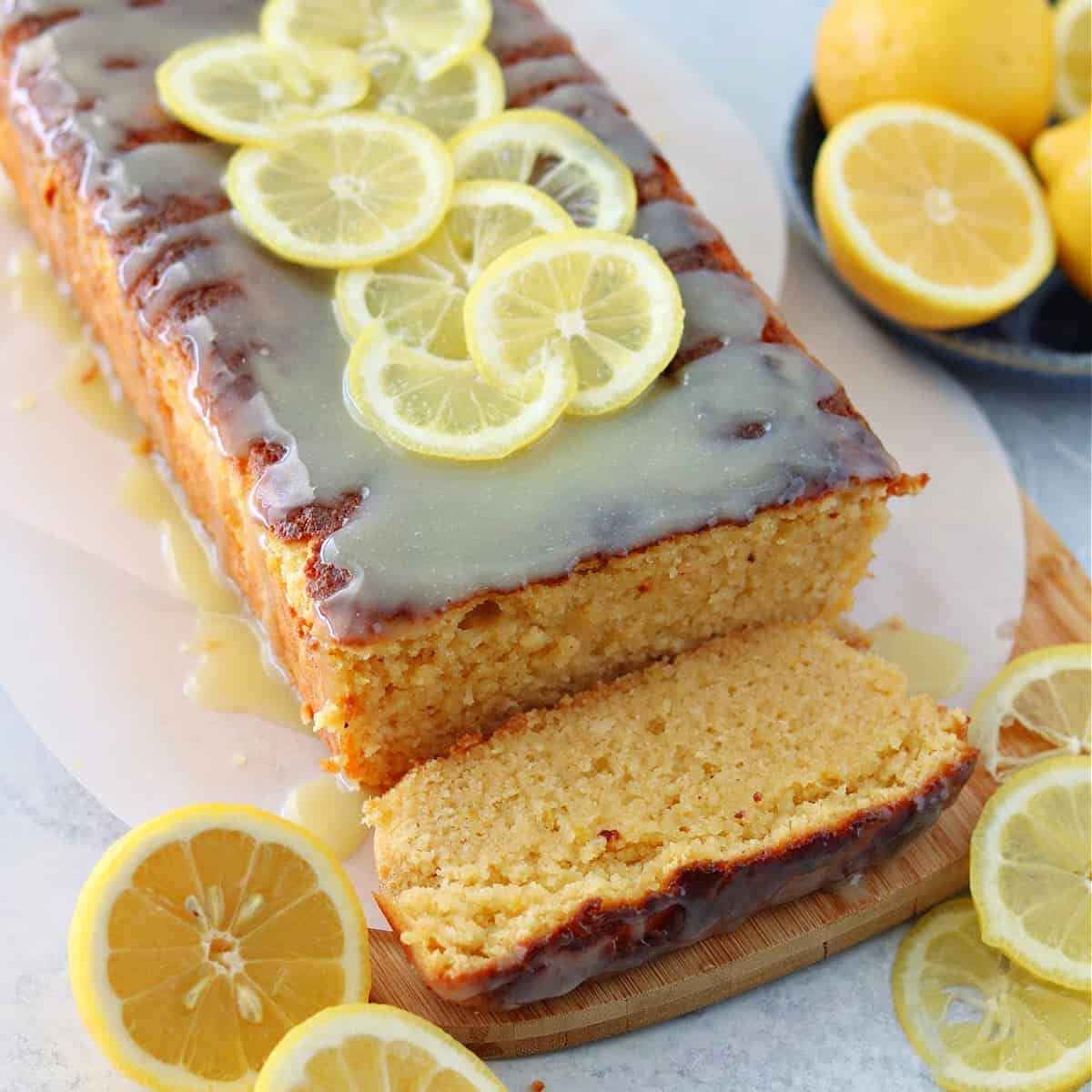 a close up of keto lemon cake with lemons topped with a sugar-free white chocolate glaze on top of a brown cutting board